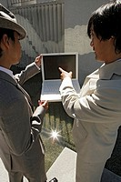 Two men are discussing about a laptop