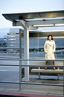 A woman is standing on a bench under a shelter