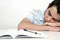 View of a teenage boy sleeping in front of study work