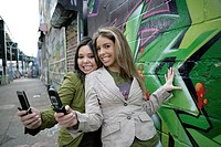 Portrait of two women with its cellphone