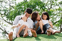 Young family sitting on ground at the park