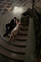 Couple sitting on step in formal attire