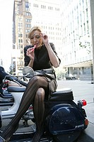 Businee woman applying lipstick on a scooter