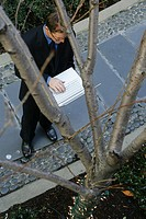 Business man standing on a path, using a laptop