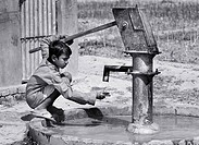 Boy pumping water from well, Allahabad. Uttar Pradesh, India