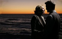 Mature couple embracing at the beach at night