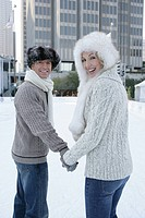 Mature couple holding hands on an ice skating rink