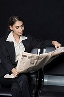 Businesswoman sitting on a bench and reading a newspaper
