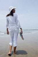 Rear view of a young woman holding flip-flop and walking on the beach