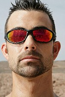 Portrait of man outside wearing reflective sunglasses (thumbnail)