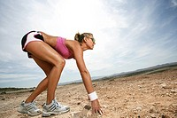 Caucasian woman in a sprinters starting position outdoors