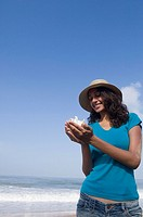 Young woman standing on the beach and holding a conch shell
