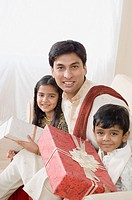 Portrait of a young man sitting with his son and daughter and holding diwali gifts