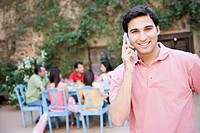 Portrait of a young man talking on a mobile phone and his friends sitting at a dining table in the background