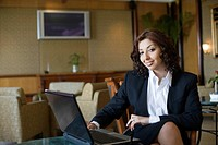 Portrait of a businesswoman sitting in front of a laptop and smiling