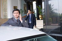 Businessman standing near a car and talking on a mobile phone