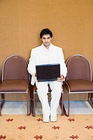 Portrait of a businessman sitting on a chair and using a laptop