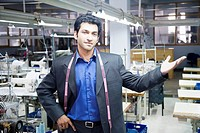 Portrait of a male fashion designer standing in a textile industry
