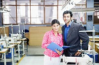 Portrait of a businessman standing with a female fashion designer in a textile industry