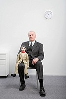 A businessman holding a ventiloquists dummy