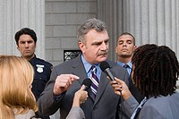 A man talking to reporters outside a courthouse