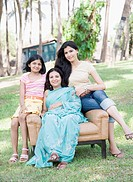 Mature woman sitting in an armchair with her two daughters in a park