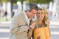 A woman showing a man contents of a shopping bag