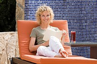 A woman sitting on a sun lounger