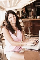 Portrait of a mid adult woman using a laptop and smiling