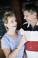 Mature woman holding an ice-cream cone with a senior man smiling beside her