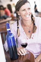 Mid adult woman sitting at a table and holding a glass of wine