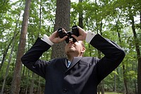 Young businessman looking through binoculars in forest