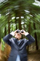 Young businessman in forest looking through binoculars