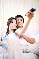 Young couple sitting on sofa and holding remote control