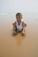 Boy playing in sand, smiling