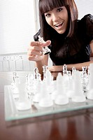 Portrait of a young woman playing chess