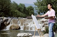 Young man painting near waterfall