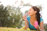 Young woman blowing bubbles, smiling