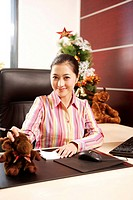 Portrait of a young woman sitting at desk in office, smiling
