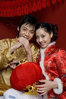 Portrait of young couple holding Chinese lantern