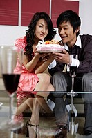 Portrait of young couple holding birthday cake, smiling