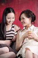 Young woman holding glass of juice and talking to friend, smiling