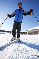 Boy wearing ski goggles with skis and ski poles