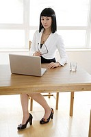 Portrait of a businesswomen holding eyeglasses by laptop