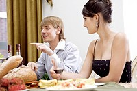 Young man and woman with food and wineglass
