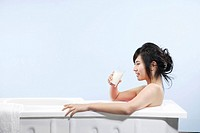 Young woman sitting in bathtub and holding glass of milk