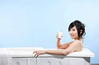 Portrait of a woman sitting in bathtub and holding glass of milk