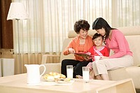Grandmother, Mother and daughter reading in sofa in front of food at home