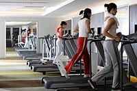 Young men and young women walking on treadmill in gym