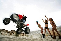 Three women watching a man on a ATV